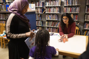 "Sanari gets her copy of the book, ""Under My Hijab,"" signed by children's book author Hena Khan at the public library in Takoma Park, Maryland, Thursday, Feb. 28, 2019."